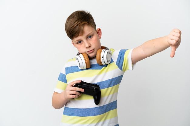 Mały rudy chłopiec trzymający konsolę do gier na białym tle pokazując kciuk w dół z negatywnym wyrazem twarzy