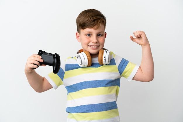 Mały rudy chłopiec trzymający konsolę do gier na białym tle robi silny gest