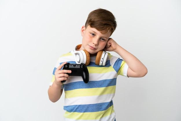 Mały rudy chłopiec trzymający konsolę do gier na białym tle sfrustrowany i zakrywający uszy