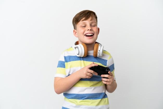 Mały rudy chłopiec trzymający konsolę do gier na białym tle śmiejąc się