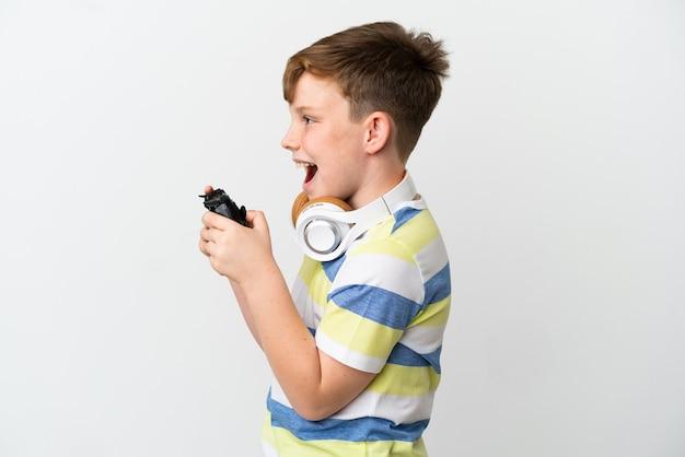 Mały rudy chłopiec trzymający konsolę do gier na białym tle śmiejący się w pozycji bocznej