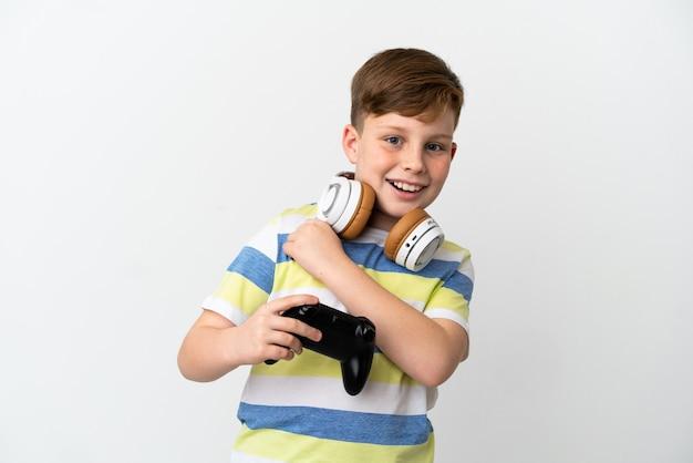 Mały rudy chłopiec trzymający konsolę do gier na białym tle świętujący zwycięstwo