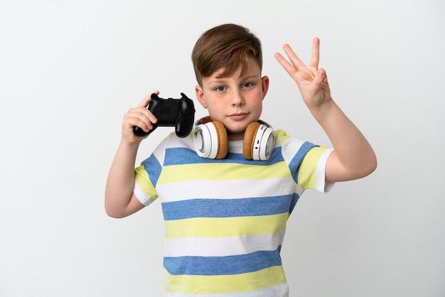 Mały rudy chłopiec trzymający konsolę do gier na białym tle szczęśliwy i liczący trzy palcami