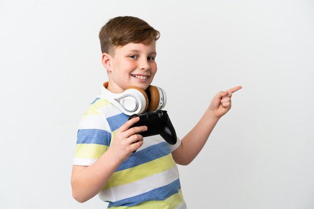 Mały rudy chłopiec trzymający konsolę do gier na białym tle wskazujący palec w bok i prezentujący produkt