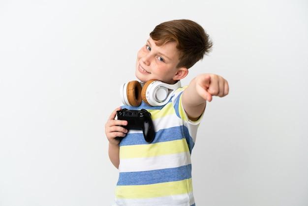 Mały rudy chłopiec trzymający konsolę do gier na białym tle wskazujący przód ze szczęśliwym wyrazem twarzy