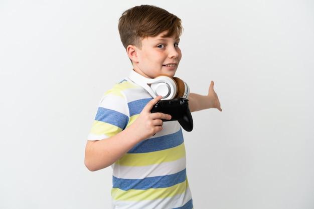 Mały rudy chłopiec trzymający konsolę do gier na białym tle wyciągając ręce do boku, aby zaprosić do siebie