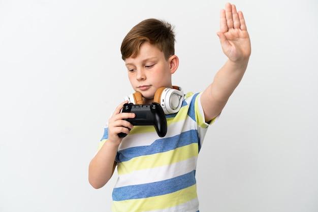 Mały rudy chłopiec trzymający konsolę do gier na białym tle, wykonując gest zatrzymania i rozczarowany