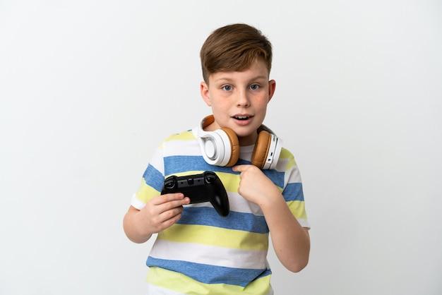 Mały rudy chłopiec trzymający konsolę do gier na białym tle z niespodzianką wyrazem twarzy