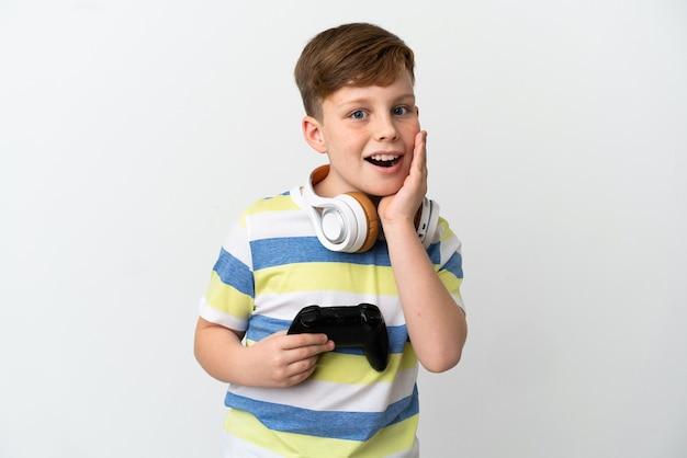 Mały rudy chłopiec trzymający konsolę do gier na białym tle z zaskoczeniem i zszokowanym wyrazem twarzy