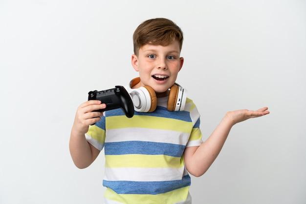 Mały rudy chłopiec trzymający konsolę do gier na białym tle ze zszokowanym wyrazem twarzy