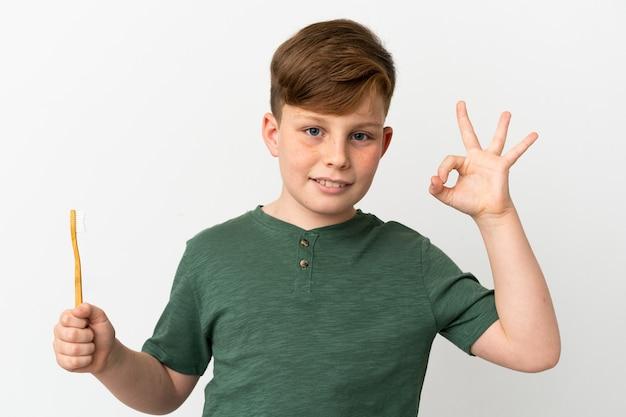 Mały rudy chłopiec trzymający szczoteczkę do zębów na białym tle pokazujący znak ok palcami