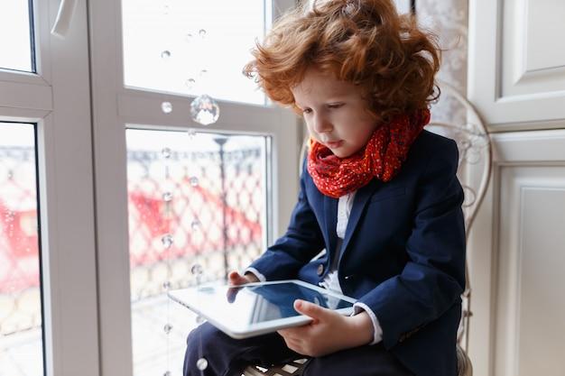 Mały rudy chłopiec używa tabletu pc