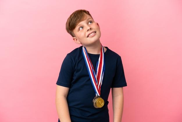 Mały rudy chłopiec z medalami na białym tle na różowym tle, patrząc w górę, uśmiechając się