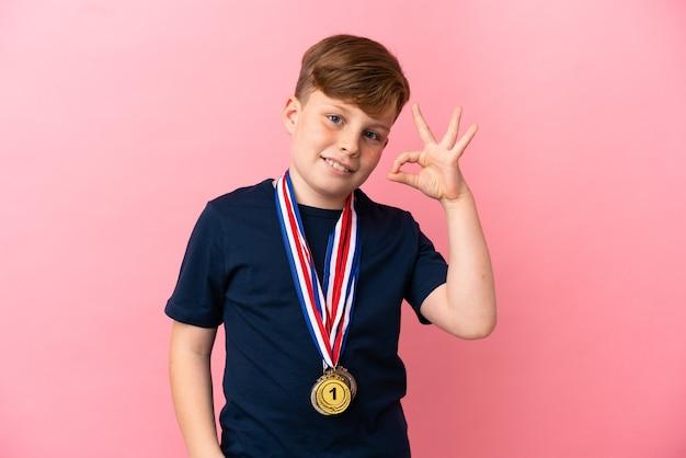 Mały rudy chłopiec z medalami na białym tle na różowym tle pokazującym znak ok palcami