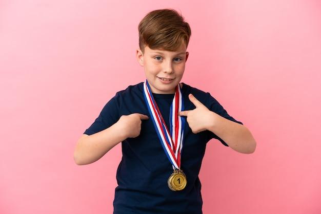 Mały rudy chłopiec z medalami na białym tle na różowym tle z niespodzianką wyrazem twarzy