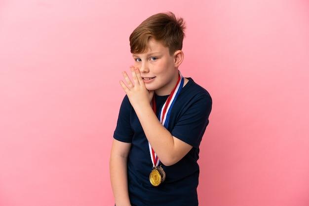 Mały rudy chłopiec z medalami na różowym tle szepczący coś