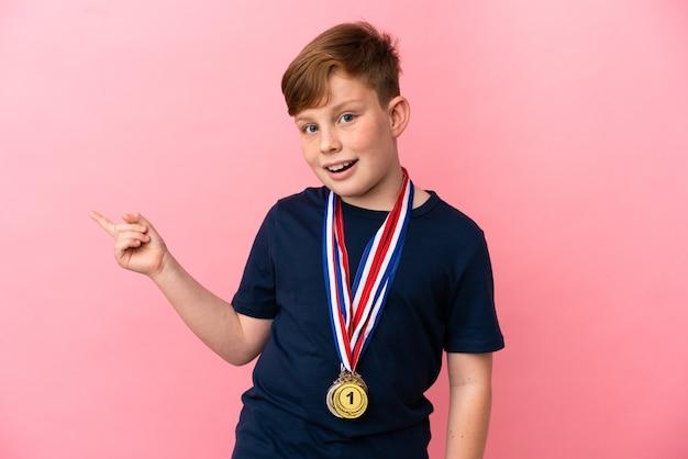 Mały rudy chłopiec z medalami na różowym tle zaskoczony i wskazujący palcem w bok