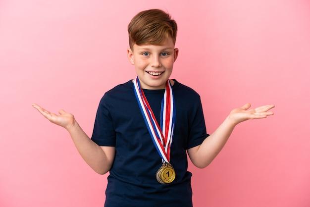 Mały rudy chłopiec z medalami na różowym tle ze zszokowanym wyrazem twarzy