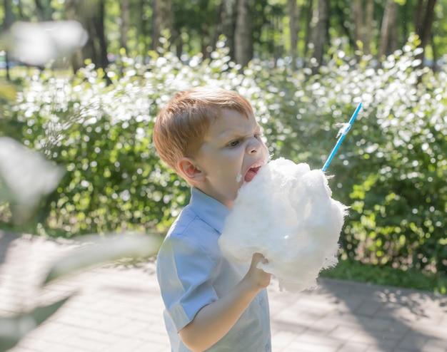 Mały rudy chłopiec z waty cukrowej