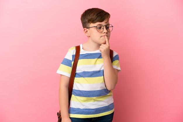 Mały rudy kaukaski chłopiec na białym tle na różowym tle, mający wątpliwości podczas patrzenia w górę