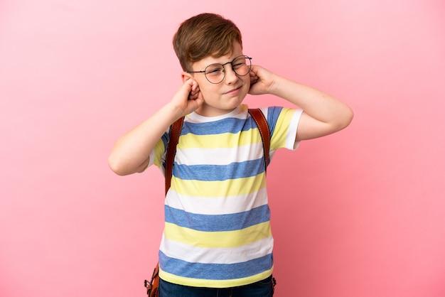 Mały rudy kaukaski chłopiec na różowym tle sfrustrowany i zakrywający uszy