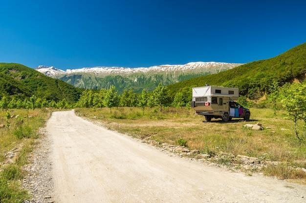 Mały samochód kempingowy samochód kempingowy jest zaparkowany pod ogromną formacją górską turystyka wakacje i podróże