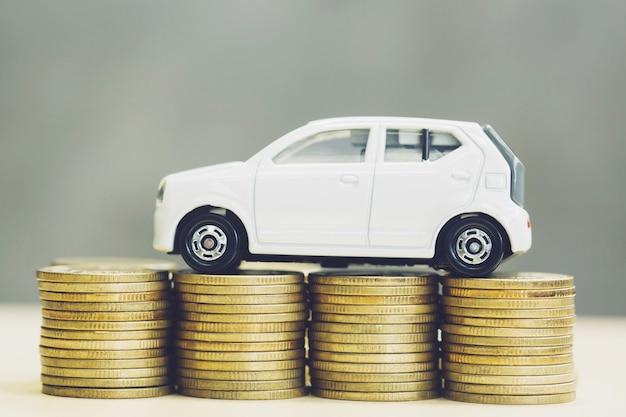 Mały samochód na wiele pieniędzy ułożonych w stosy monet