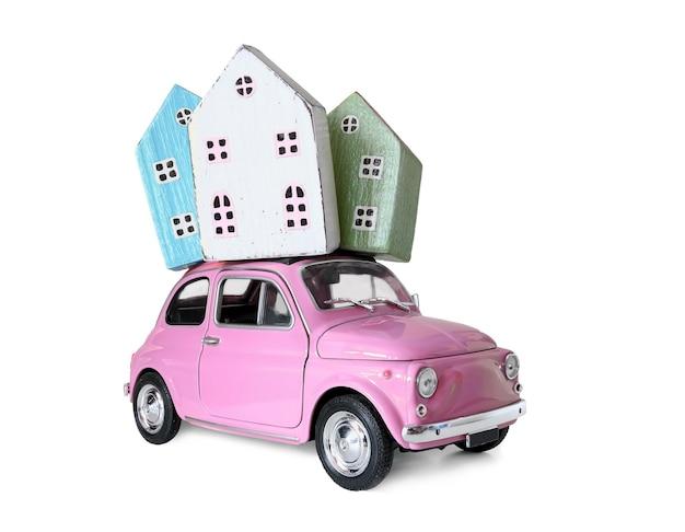 Mały samochód retro z miniaturowymi modelami domów na dachu. koncepcja nieruchomości, hipoteka, kupno sprzedam dom, przeprowadzka