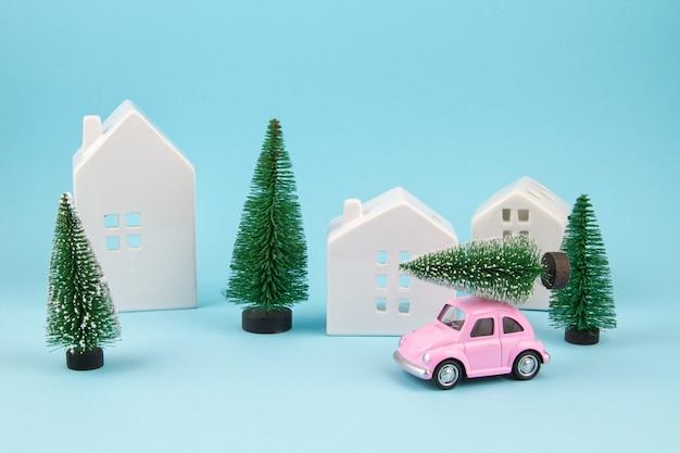 Mały samochodzik przewożący choinki nad dachem. sezonowe wakacje, karta z pozdrow
