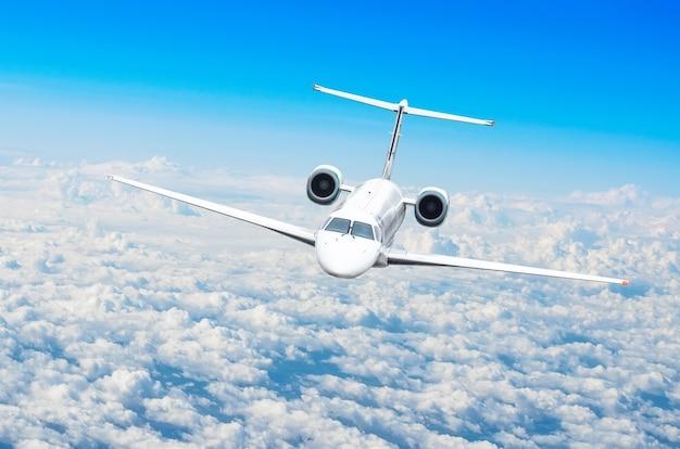 Mały samolot pasażerski leci na niebie nad chmurami.