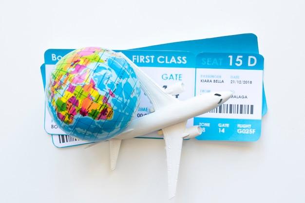 Mały samolot z biletami i kulą ziemską