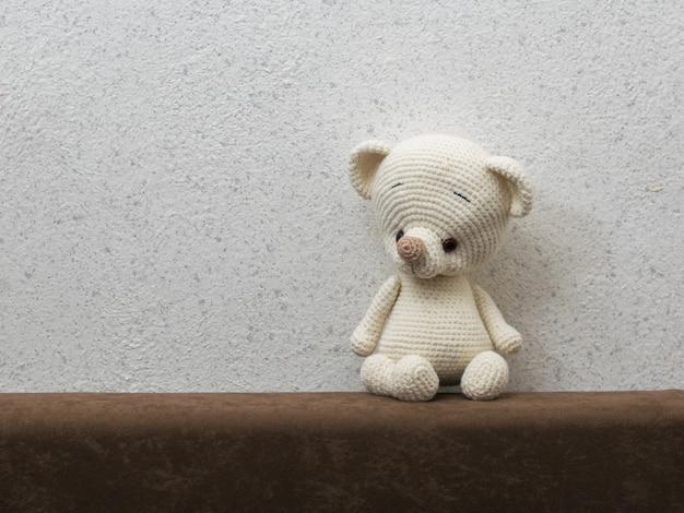 Mały, samotny niedźwiadek z tyłu sofy przy szarej ścianie. piękna dzianinowa zabawka.