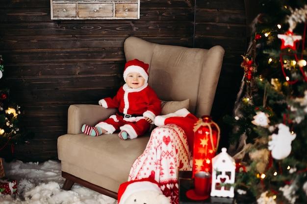 Mały santa ładny chłopiec w czerwonym apartamencie i czapce siedzi w dużym fotelu w pobliżu choinki