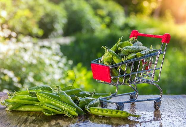 Mały sklep spożywczy wózek z zielonymi groszkami na naturalnym tle