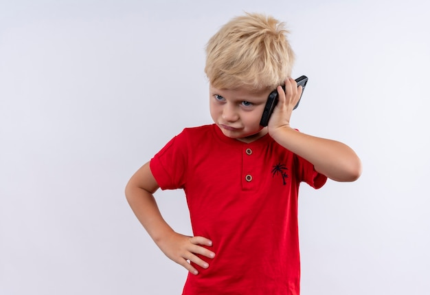 Mały śliczny blond chłopiec w czerwonej koszulce mówi na telefonie komórkowym ręką na talii na białej ścianie