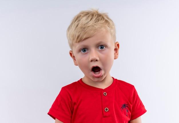 Mały śliczny blond chłopiec w czerwonej koszulce zaskakuje patrząc na białą ścianę