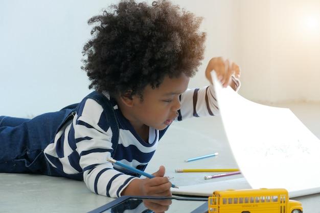 Mały śliczny chłopiec kłaść się rysować na papierze w szkole. amerykanina afrykańskiego pochodzenia pojęcie.