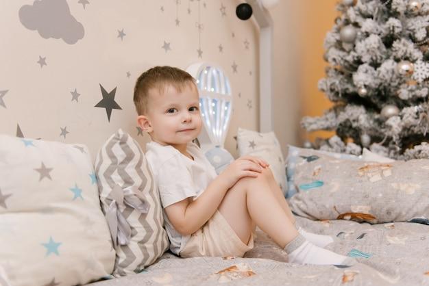 Mały śliczny chłopiec siedzi w pokoju dziecięcym w drewnianym domku z lampkami nocnymi w kształcie balonu obok choinki