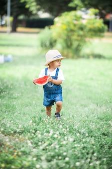 Mały śliczny chłopiec spacery po lesie. mały chłopiec je arbuza. lato.