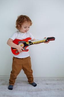Mały śliczny chłopiec w białej koszulce gra na gitarze zabawkowej