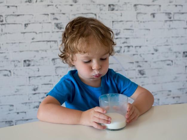 Mały śliczny chłopiec w niebieskiej koszulce pije mleko