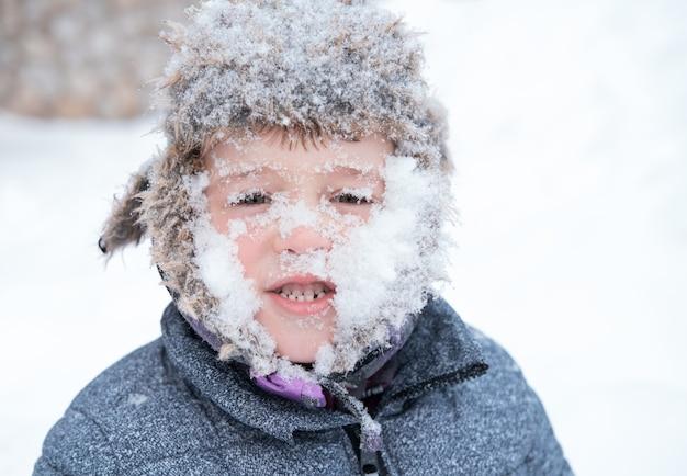 Mały śliczny chłopiec w zimowej czapce z śnieżną twarzą.