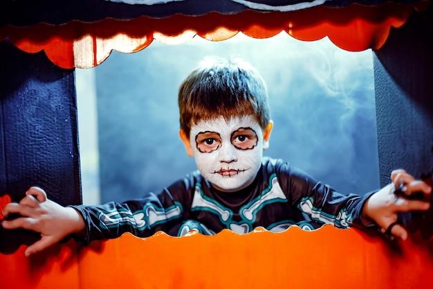 Mały śliczny chłopiec z facepaint jak szkielet, aby świętować halloween