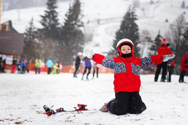 Mały śliczny chłopiec z nartami i strój narciarski