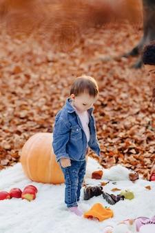 Mały śliczny dziecko w parku na żółtym liściu z banią w jesieni