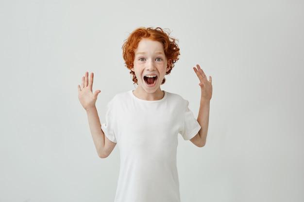 Mały śliczny rudy chłopiec z piegami w białej koszulce jest bardzo zaskoczony i szczęśliwy