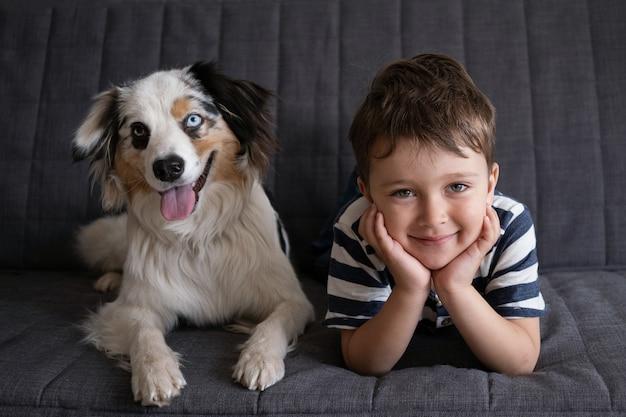 Mały śliczny szczęśliwy chłopiec z psem owczarek australijski blue merle. najlepsi przyjaciele. miłość i przyjaźń między człowiekiem a zwierzęciem.