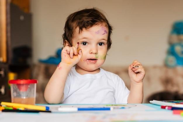 Mały słodki chłopiec rysuje pędzlami i kolorowymi farbami na kartce papieru