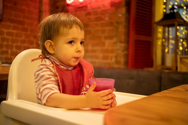 Mały słodki dzieciak siedzi w krzesełku trzyma w dłoniach szklankę soku i pije