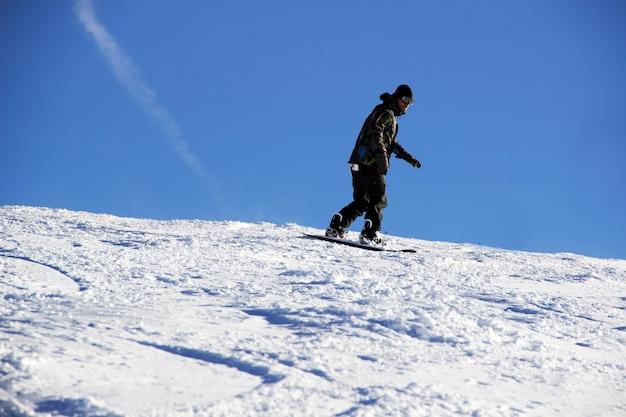 Mały snowboardzista na tle niebieskiego nieba.